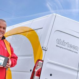 A man holding a tablet in front of a Thirteen services van.