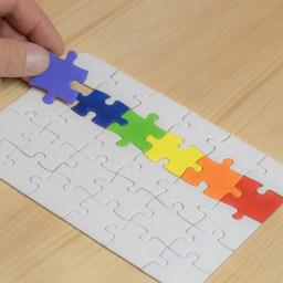 A hand laying down pieces of a jigsaw puzzle coloured like the LGBT flag.