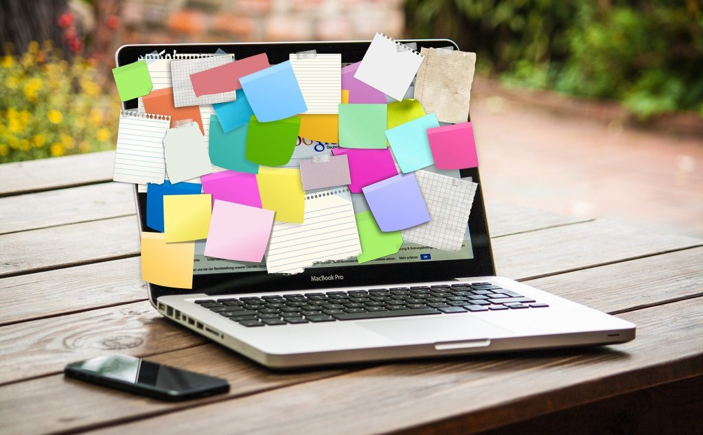 A Macbook covered in post-it notes. The Google homepage is shown on the screen.