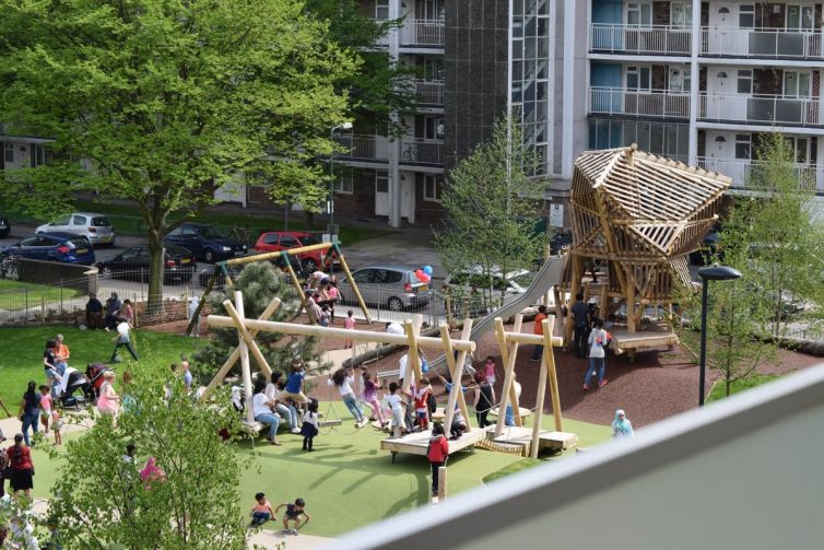 An urban park and playground surrounded by residential tower blocks.
