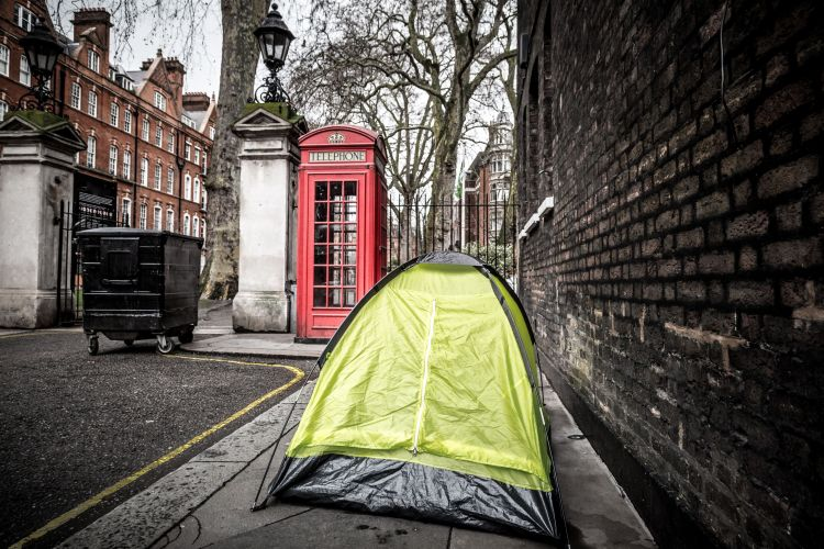 Color image depicting a small tent on the pavement of the city street in London, UK, with a homeless person sleeping inside.