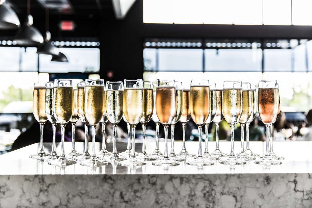 Photo of Champagne flutes filled with bubbles on the bar.