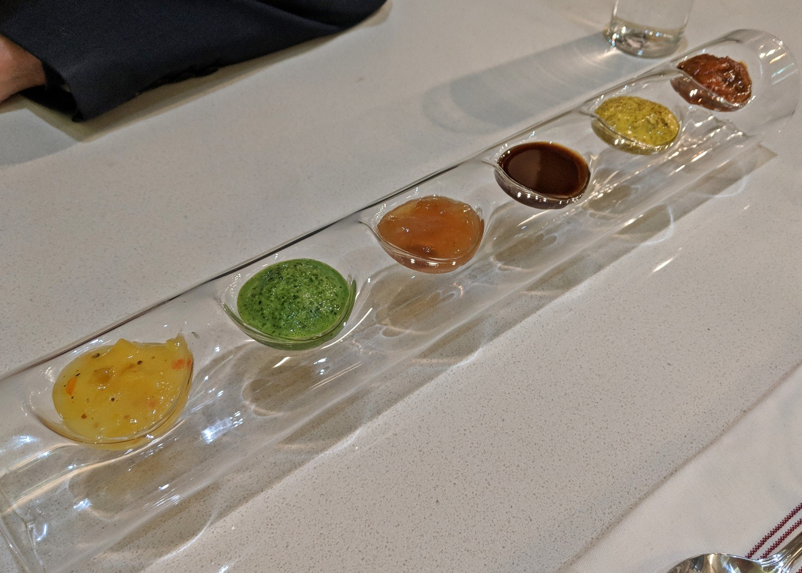 Long clear tray with six sauces in yellow, green, oranges and browns.