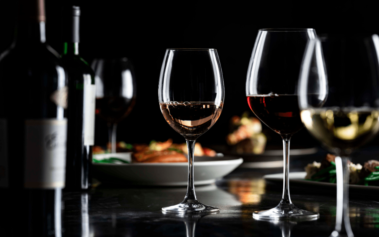 Low-light photo of two wine bottles and several wine glasses with wine and a plate of food in the background