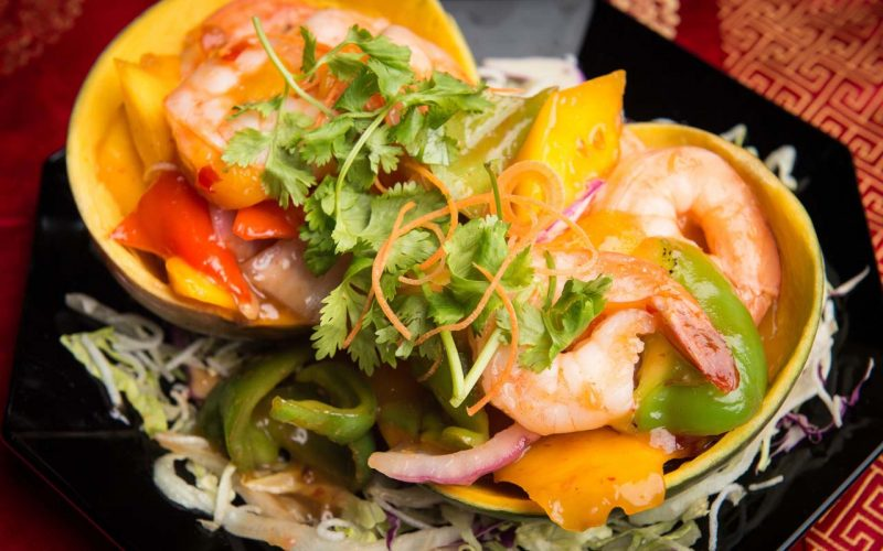 Mango shells filled with shrimp, mango chunks and vegetables topped with cilantro.