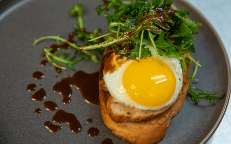 Toast with sunny-side up egg, greens, and sauce