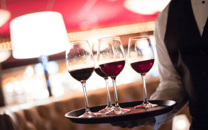 Multiple glasses of red wine on serving tray held by a partially visible waiter.