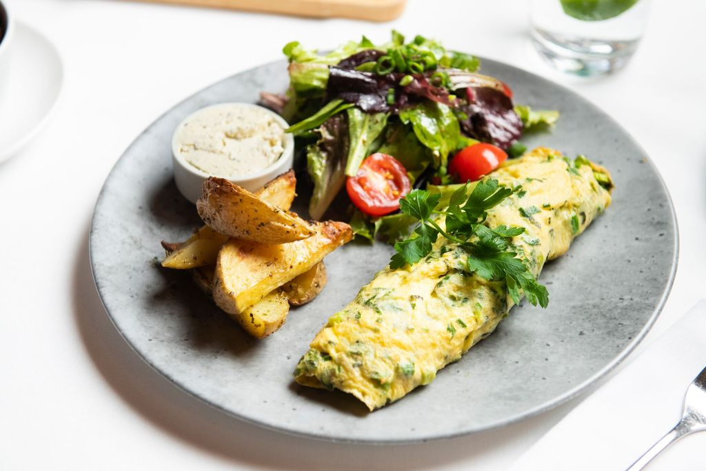 Photo of an omelette on a plate with a mixed green salad and potato wedges.