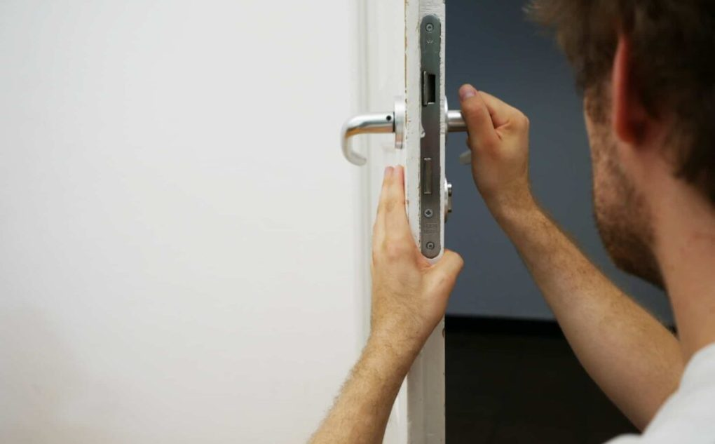 locksmith tech holding a handle of a commercial lock on a door for changing it and rekey it