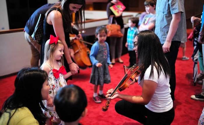 Children admire musicians' instruments in the Jones Hall lobby.