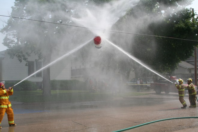 Competing fire teams attempt to push the 25-gal. drum back to their opponent's engine.