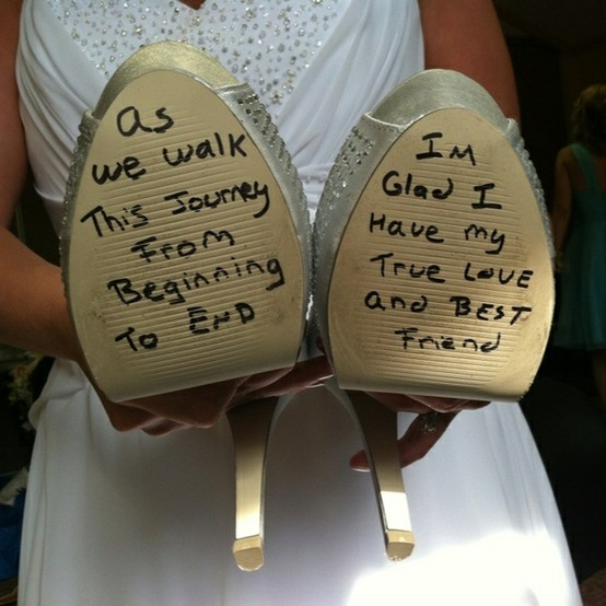 the groom writes on the brides shoes before the wedding