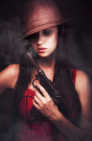 Stock image of 'Sexy woman mobster with her hat pulled low over her eyes tot