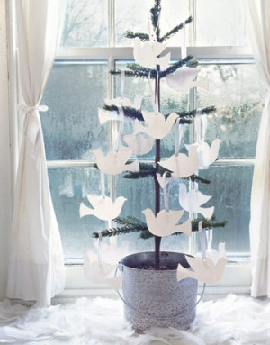 "Pure white doves flock en masse to the miniature tree's branches, proclaiming ""peace on Earth."" Cut your own from white card stock and hang from lengths of ribbon, or use dove-shaped gift tags for a quicker solution. In keeping with the humble theme, the tree sits inside a pale blue-painted galvanized bucket."