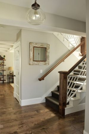 Sherwin Williams Repose Gray is a beautiful light gray paint colour with subtle undertones. Shown with wood flooring going up stairs