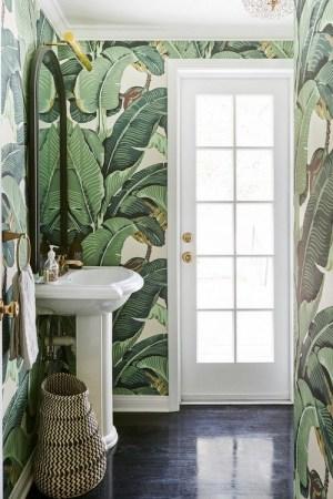 A bright bathroom with banana leaf wallpaper