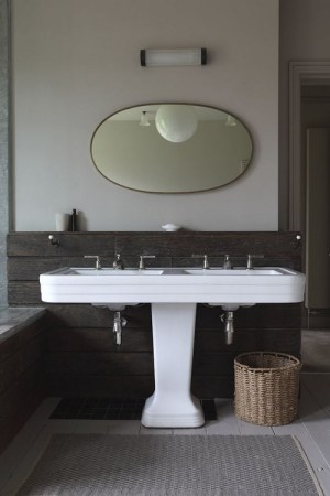 Beautiful double pedestal sink and oval mirror.