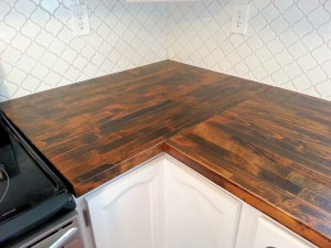 l-shaped-kitchen-cabinet-with-butcher-block-countertop-and-white-backsplash-for-chic-kitchen-decor-idea