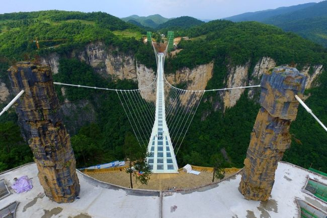the-430-meter-long-6-meter-wide-bridge-paved-with-99-panes-of-three-layer-transparent-glasses-hangs-between-two-steep-cliffs-300-meters-above-the-ground