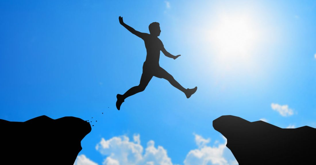 man jumping across a small chasm