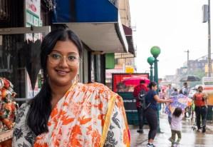 Meet Shahana Hanif, Hanif smiling at the camera in front of a Brooklyn street.