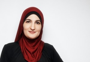 Meet Linda Sarsour, portrait of Sarsour looking at the camera, wearing a red hijab.