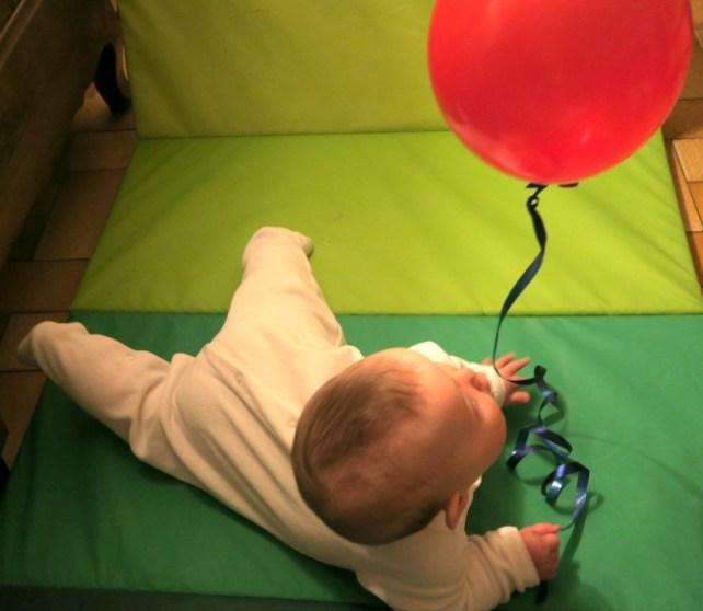 bébé joue avec ballon baudruche gonflé hélium