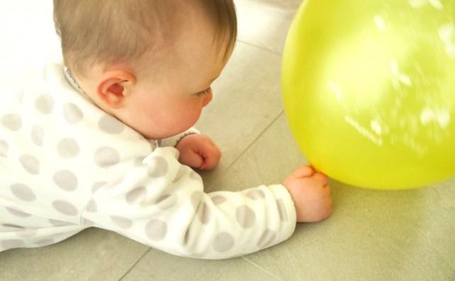 bébé joue avec ballon de baudruche