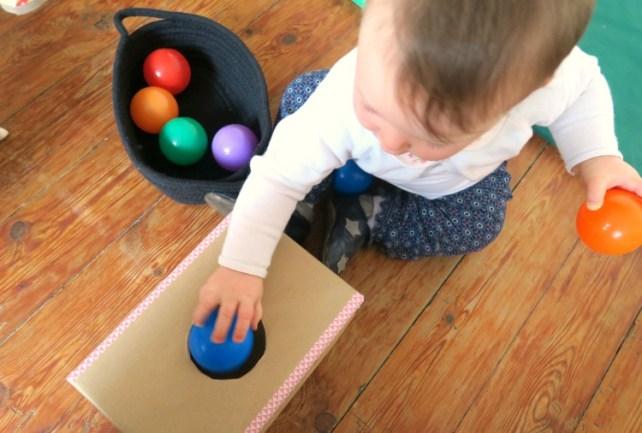 bébé joue avec balle dans boite permanence objet