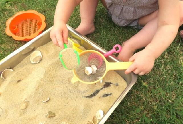transvasement sable avec tamis bac sensoriel Montessori