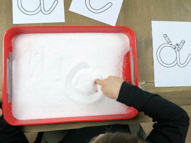 Jeu d'écriture tracer des lettres dans du sel ou sable