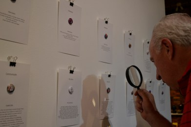 Attendees use magnifying glasses to view micro-art on 1-inch pin-back buttons.