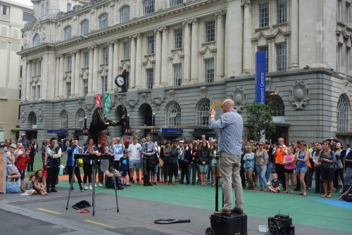 Amazing street entertainer in Auckland, shooting a bow and arrow with her feet (!) after contorting herself through a tennis racket