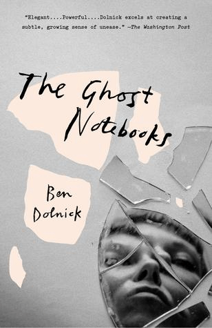 Cover of The Ghost Notebooks by Ben Dolnick. Cover is plain grey, and shows shards of a broken mirror in the bottom right corner. A face is reflected in the mirror shards.