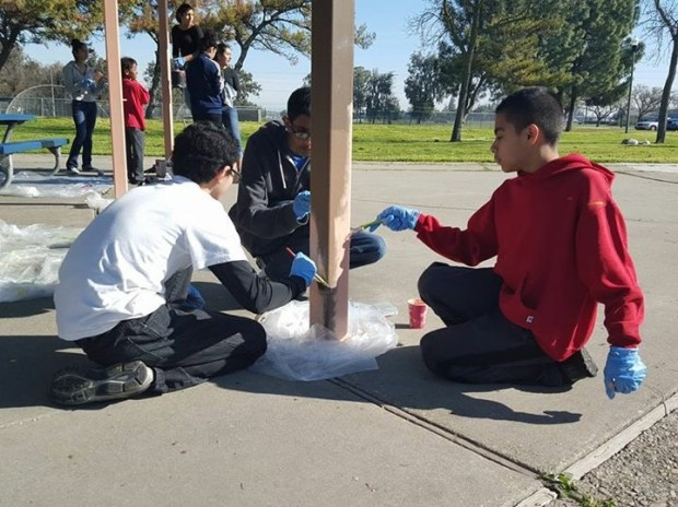 Youth painting a picnic area of a park