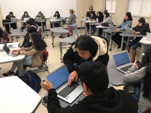Woman helping a high school student working a laptop. Other students are in the room working on laptops.