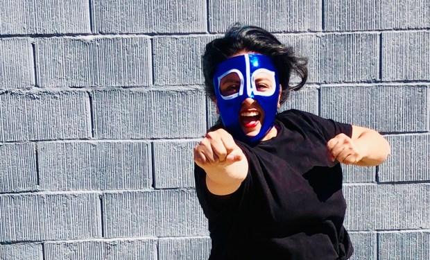 Woman wearing a blue luchadora mask in a superhero stance