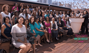 Large group of women sitting on patio, smiling and side by side, looking at camera