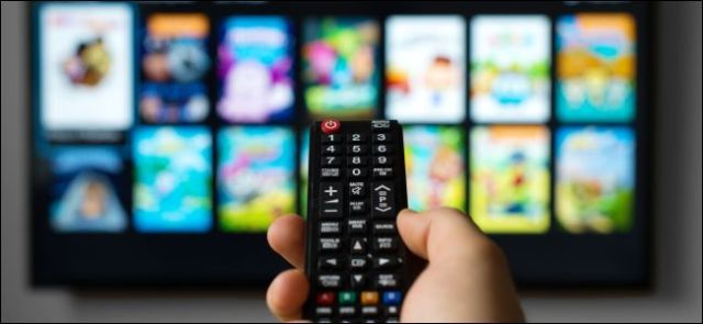 man holding a remote control pointing at the television