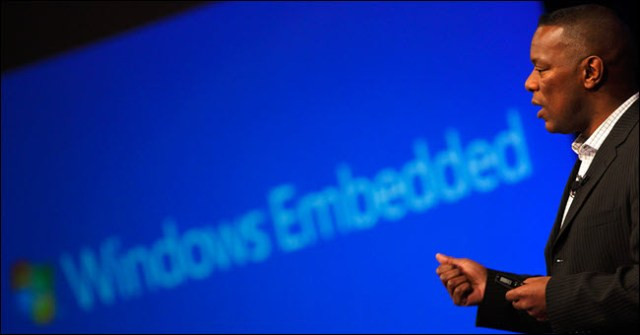 Man speaking in front of the Windows Embedded logo.