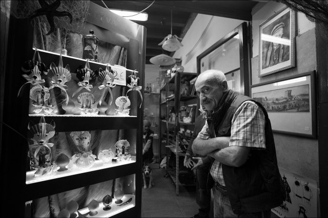 An Italian in a shop, standing in front of a shelf of trinkets and glass figurines.
