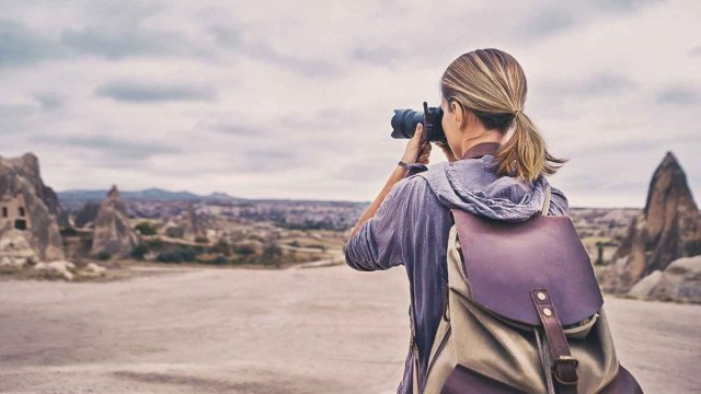 Woman taking pictures of a hilly landscape.