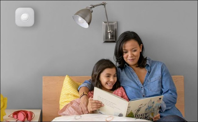 A mother and child read a children's book in bed with a Nest Protect mounted on the wall above their head.
