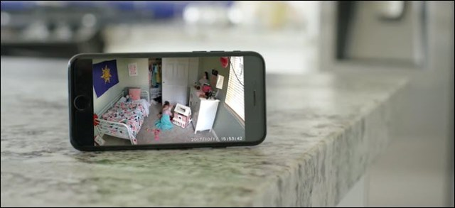 An iPhone showing a Wyze Cam stream of a child playing in his room.