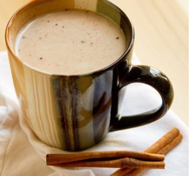 A cup filled with hot cinnamon tea and two cinnamon sticks next to it.