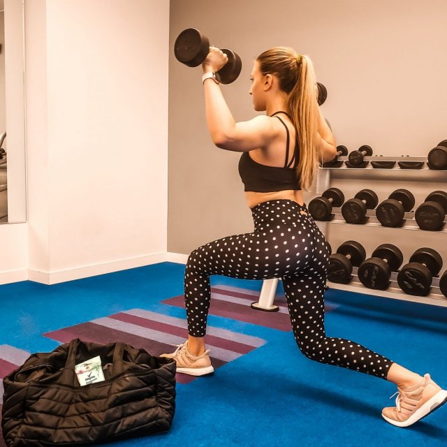 Woman working out at weights in gym