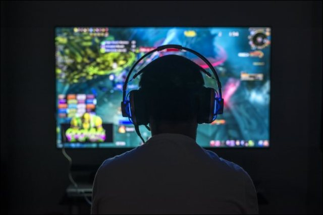 A young player playing a PC game while wearing headphones.