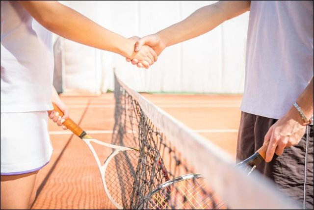 Two players shaking hands on a tennis court
