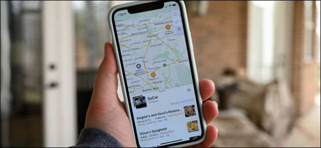 A hand holding an iPhone with an Apple Maps collection on the screen.
