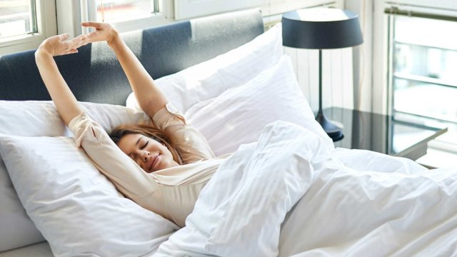 Woman stretching in bed, waking up with her favorite song.